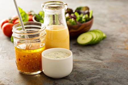 Verscheidenheid aan zelfgemaakte sauzen en dressings in kruiken met inbegrip vinaigrette, ranch en honing mosterd Stockfoto