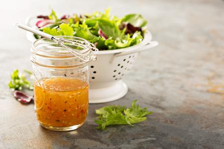 Vinagreta italiana en un frasco de vidrio con verduras frescas en la mesa Foto de archivo - 71098462