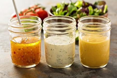 Varietà di salse fatte in casa e condimenti di insalata nei vasi di muratore, tra cui la vinaigrette, la ranch e la senape di miele