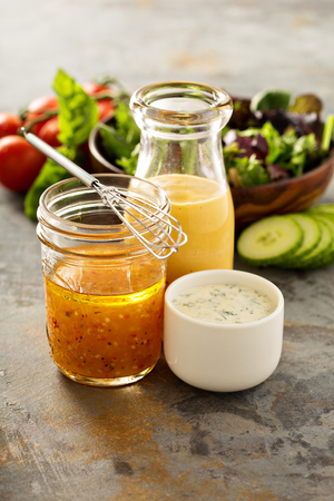 Variety of homemade sauces and salad dressings in jars including vinaigrette, ranch and honey mustard Banco de Imagens - 71098366