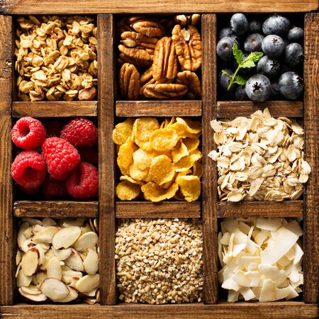 Breakfast foods, oats, cereals and fruit in a wooden box overhead shot