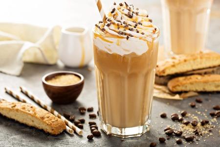 Café con leche helado con caramelo en un vaso alto con jarabe y crema batida