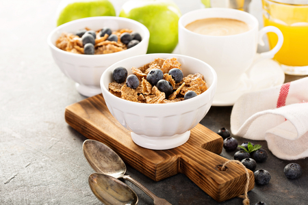 Multigrain wholewheat healthy cereals with fresh blueberry, coffee and orange juice for breakfast