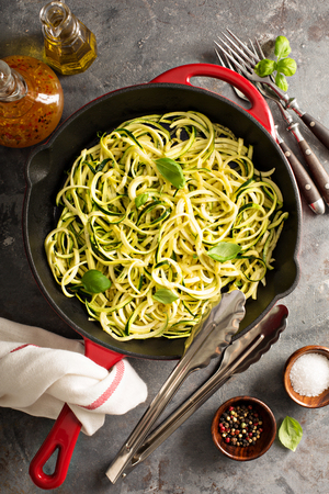 spiralized: Cooked spiralized zucchini noodles in a cast iron pan overhead view, low carb dish Stock Photo