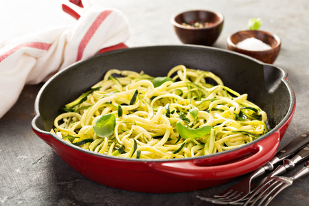 Cooked spiralized zucchini noodles with basil in a cast iron pan, low carb dish
