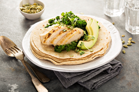 Making tacos with kale, grilled chicken and avocado