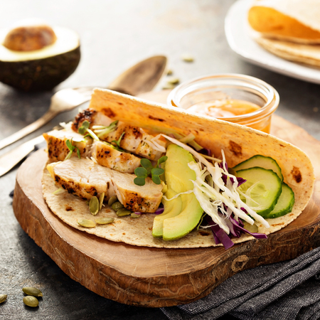 Making tacos with fresh vegetables, grilled chicken and avocado Stock Photo