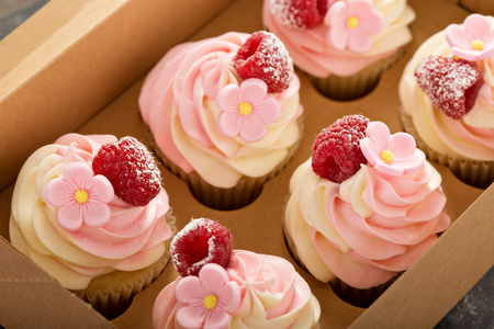 Pink vanilla and raspberry cupcakes with sugar flower in a craft box