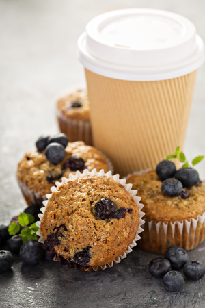 Healthy vegan banana blueberry muffins with coffee in a paper cup