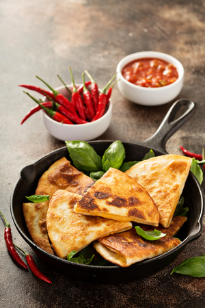Cheese quesadillas in a cast iron pan with tomato salsa