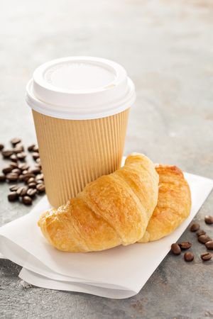 Croissants with coffee to go in a paper cup, take away breakfast Stock Photo