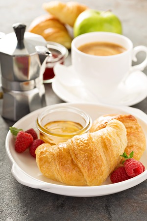 Freshly baked croissants with honey, jam and coffee for breakfast