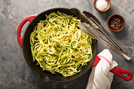 Cooked spiralized zucchini noodles in a cast iron pan overhead view, low carb dish Foto de archivo