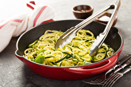 spiralized: Cooked spiralized zucchini noodles with basil in a cast iron pan, low carb dish