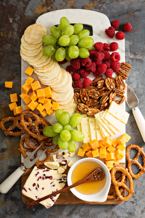 Cheese and snacks platter with honey and fresh fruit Stock Photo
