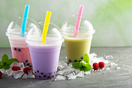 Variety of bubble tea in plastic cups with thick straws Stock Photo