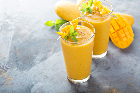 Refreshing and healthy mango smoothie in tall glasses Banco de Imagens