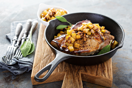 Sauteed pork chops with caramelized apples and walnuts in a cast iron pan