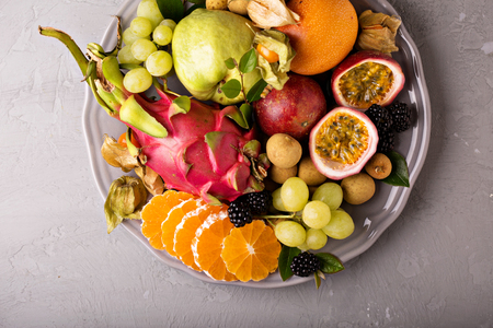 Exotic tropical fruits with dragon fruit, granadilla, maracuya on a plate overhead shot