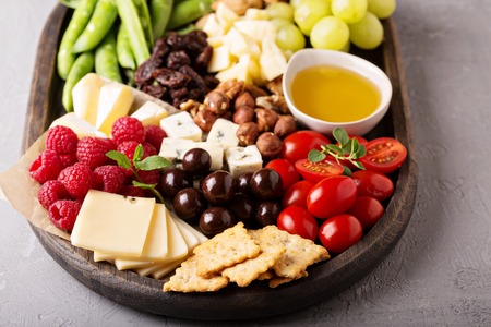 tabla de quesos: Cheese plate with nut, honey, chocolate, fresh vegetables and fruits