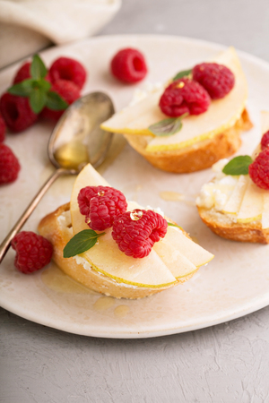 Open faced sandwiches with cheese, pears and raspberry