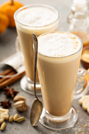 Pumpkin spice latte in tall mugs with cinnamon, nutmeg and cardamom Stock Photo
