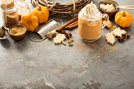 Pompoenspaghetti latte in een glazen mok met kaneel, nootmuskaat en koekjes