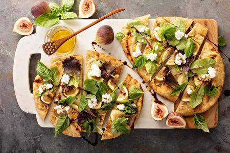 フラットブレッド秋のピッツァ バルサミコ、イチジク、チーズ、サラダの葉します。