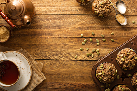 Healthy pumpkin muffins with fall spices and pumpkin seeds fall background overhead shot with copy space