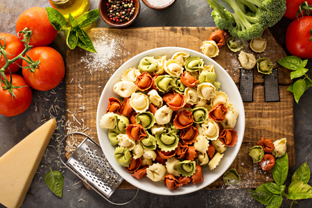 Red, white and green tortellini with vegetables and cheese