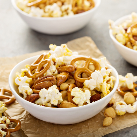 Homemade trail or snack mix with popcorn, pretzels and nuts in white bowls