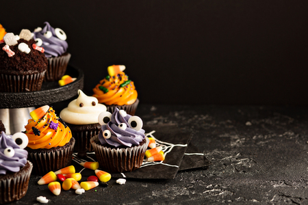 Festive Halloween cupcakes and treats decorated with sprinkles and candy, copy space
