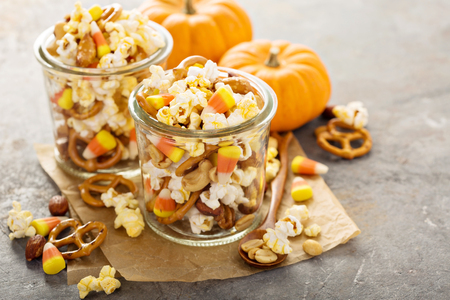 Homemade Halloween trail or snack mix with candycorn, popcorn, pretzels and nuts in glass jars Stok Fotoğraf
