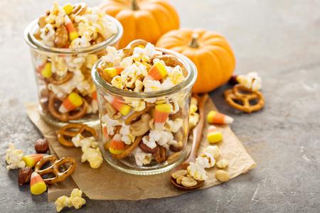 Zelfgemaakte Halloween-trail of snackmix met candycorn, popcorn, pretzels en noten in glazen potten Stockfoto