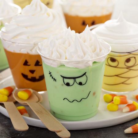 Grappige Halloween-thema puddingen in kopjes met slagroom