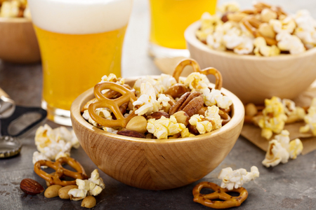 Homemade trail or snack mix with popcorn, pretzels and nuts with beer in glasses Stock Photo