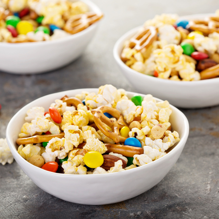 Homemade trail mix for kids with chocolate candy, popcorn, pretzels and nuts in white bowls