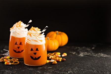 Halloween cold pumpkin cocktail or drink with jack olantern face and whipped cream