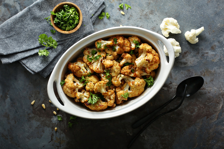 Roasted cauliflower with pine nuts and fresh parsley Фото со стока