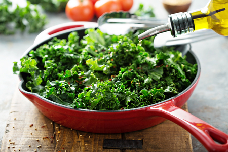 Quickly sauteed kale with chili flakes in a cast iron pan with olive oil pouring over, healthy cooking concept