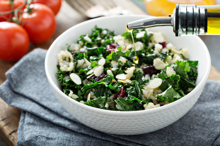 Warm kale salad with brown rice, almonds and dried cranberry with olive oil pouring over