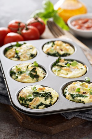 High protein egg muffins with kale and ground turkey in a muffin tin Stock Photo