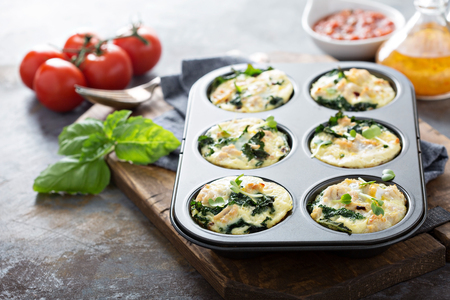 High protein egg muffins with kale and ground turkey in a muffin tin Foto de archivo