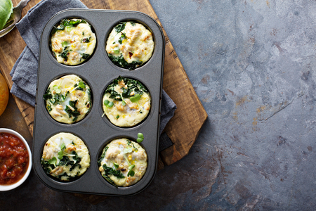 High protein egg muffins with kale and ground turkey in a muffin tin overhead shot with copyspace