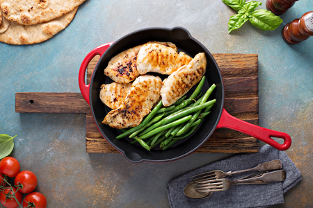 Grilled chicken with green beans in a cast iron skillet Stock Photo
