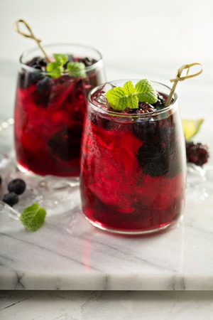 Cold summer berry drink with lime and blackberries Stock Photo