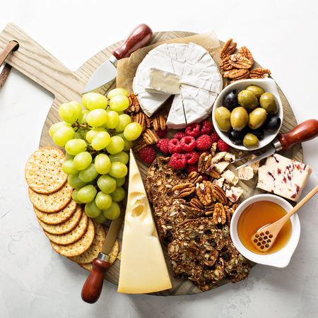 Cheese and snacks plate on white background overhead shot