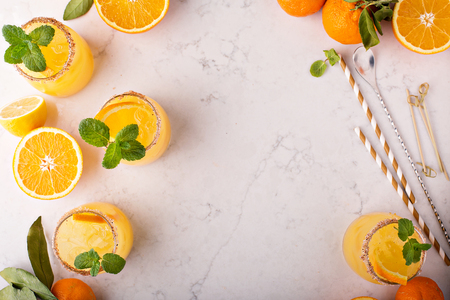 Orange and lemon margarita cocktail with mint and ice overhead shot with copyspace