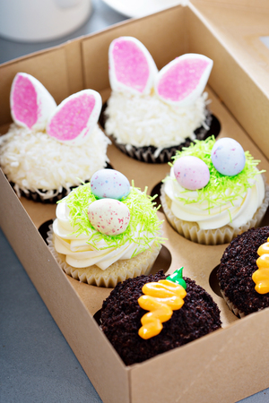 Assortment of easter cupcakes in a box with bunny ears and candy eggs