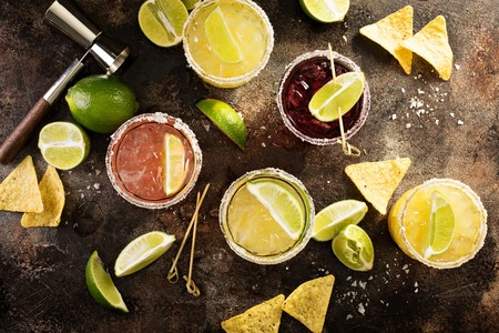 Variety of margarita cocktails with salted rim and lime on dark background overhead shot Stock Photo